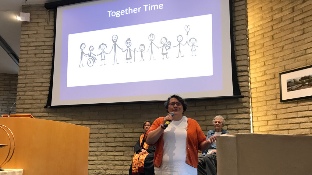 """Children's Ministry director speaking in sanctuary; """"Together Time"""" with line drawings of a row of adults and childen is a large projection screen on the wall"""