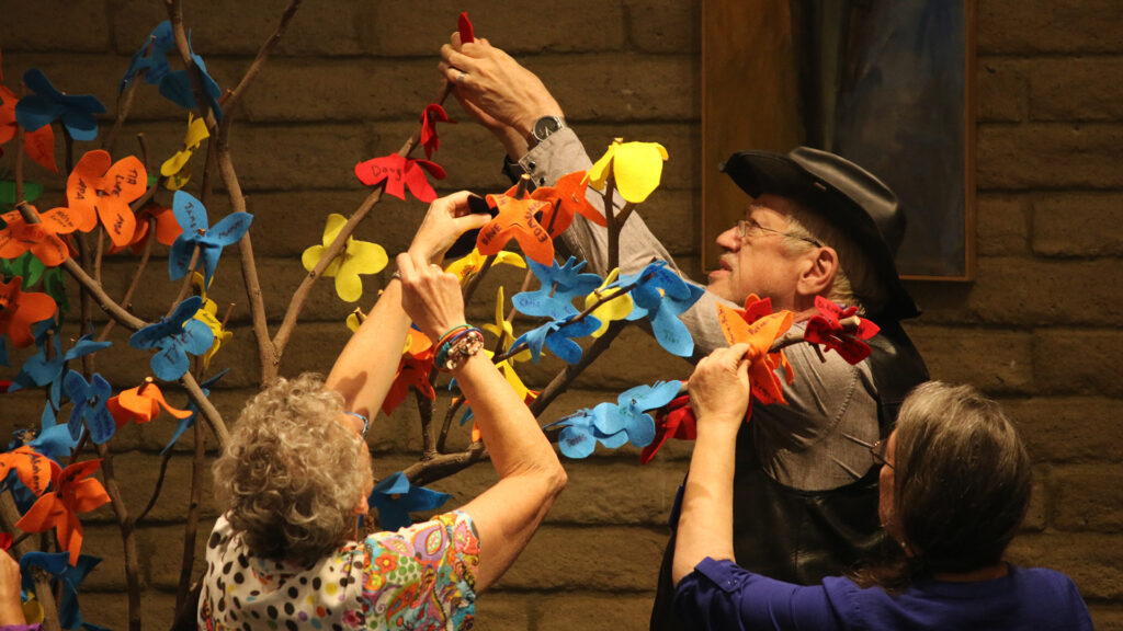 3 UUCP congregants affixing felt flowers with names and messages on them to branches in the sanctuary - Day of the Dead service
