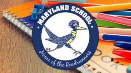 Spiral bound notebook and colored pencils on wooden desk overlaid with Maryland School logo