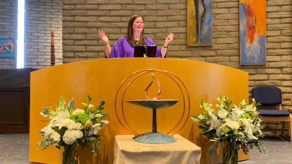 Rev Christine Dance behind altar, leading service in sanctuary