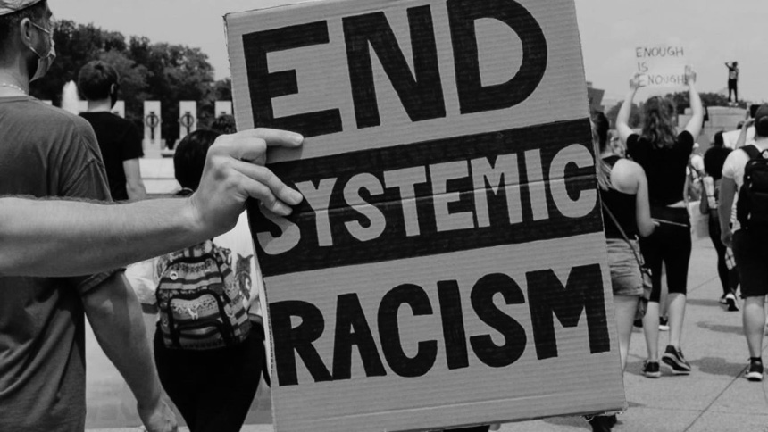 """Black & white photo - hand holding carboard sign """"END SYSTEMIC RACISM"""""""